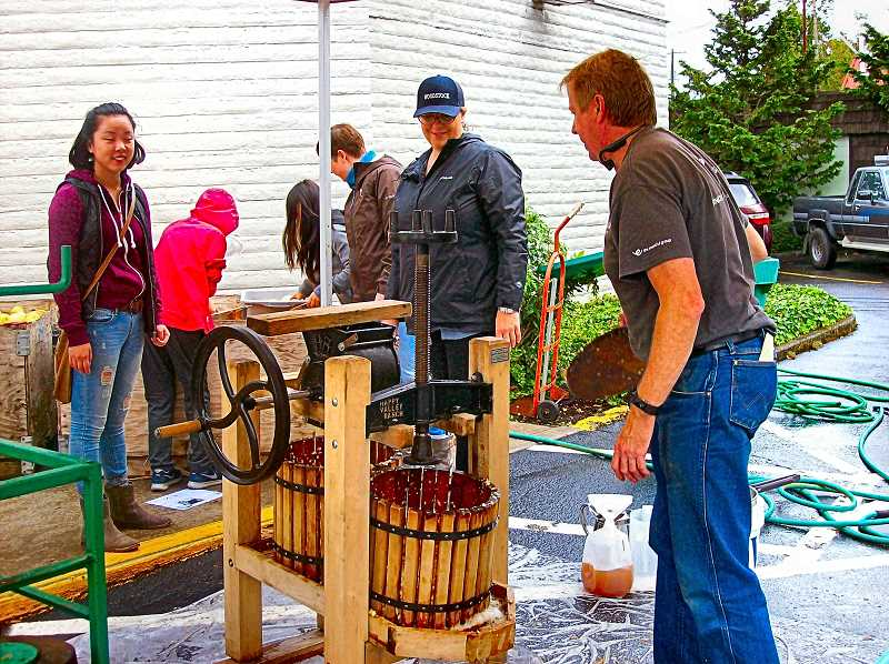 RITA A. LEONARD - Scott Farestrand, at right, co-organizer of the 2017 Woodstock Apple Festival, chatted with volunteers at the cider-press station during this years Woodstock Elementary School fundraiser.