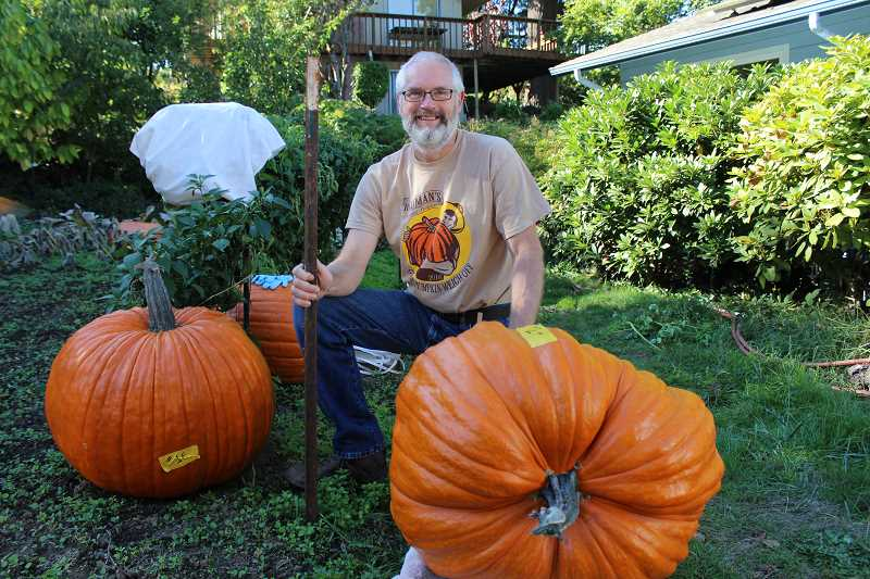 REVIEW PHOTO: SAM STITES - Jef Treece of West Linn poses with two of his giant field pumpkins. He took one of them to the weigh-off at Bauman Farms, where it tipped the scales at 120.5 pounds.
