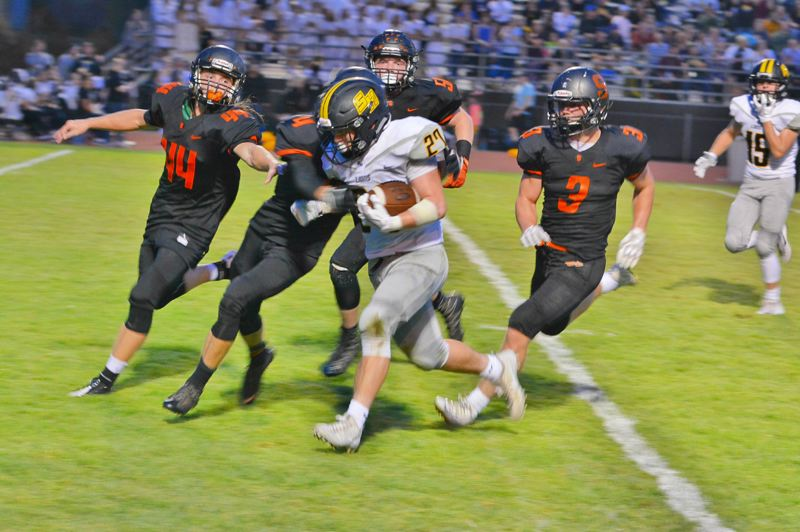SPOTLIGHT PHOTO: JAKE MCNEAL - The Indians and Lions will be conference rivals -- this time in the Class 5A Northwest Oregon Conference -- for the first time since 1999 -- effective fall 2018 through spring 2022. Pictured: St. Helens senior running back Cody Leanna (27) runs through Scappoose junior defensive back Connor McNabb (44) and senior defensive back Jimmy Jones (3) in the host Tribe's 62-6 Sept. 8 Seven-Mile War win.