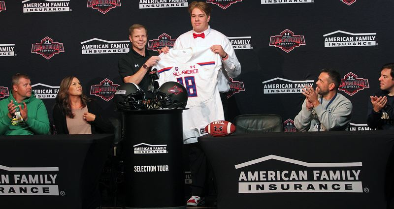 REVIEW PHOTO: MILES VANCE - Lake Oswego senior lineman Dawson Jaramillo (center) accepts a jersey signifying his selection as an Under Armour All-American from American Family Insurance agent Larry Thompson during a ceremony before friends, family, coaches, teammates and classmates at Lake Oswego High School on Friday.