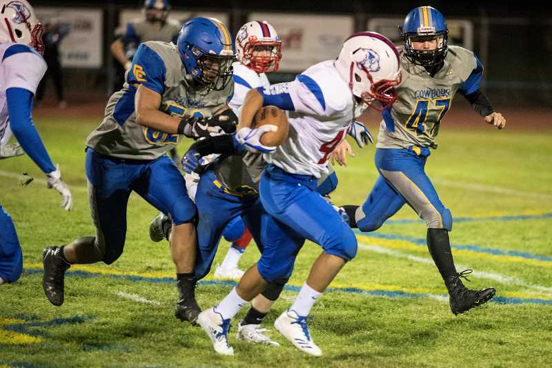 LON AUSTIN/CENTRAL OREGONIAN - Catalino LeClaire runs for some tough yardage against the Crook County Cowboys Friday night. LeClaire finished with 43 yards on three carries.