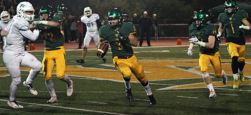 TIDINGS PHOTO: MILES VANCE - West Linn's Cody Fretwell returns an interception for a touchdown — one of his two pick-sixes in the game — during the Lions' 49-0 home win  over Lakeridge on Friday night.