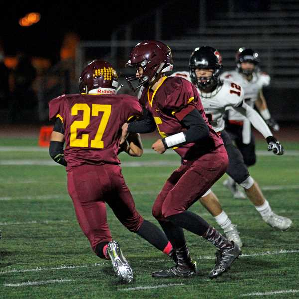 NEWS-TIMES PHOTO: WADE EVANSON - Forest Grove's Drake Littlefield takes a handoff from quarterback Jarod Miller during the Vikings' game against McMinnville Oct. 20 at Forest Grove High School.