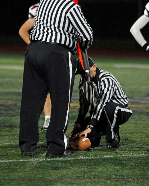 NEWS-TIMES PHOTO: WADE EVANSON - Referees measure for a first down following Forest Grove's fourth and one attempt late in the fourth quarter during the Vikings' game against McMinnville Oct. 20 at Forest Grove High School.