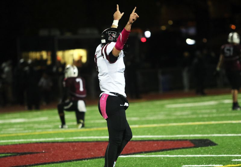 DAN BROOD - Tualatin junior quarterback Kyle Dernedde raises his hands after sophomore running back Kainoa Sayre scored on a 69-yard run late in the Wolves' win at Sherwood.