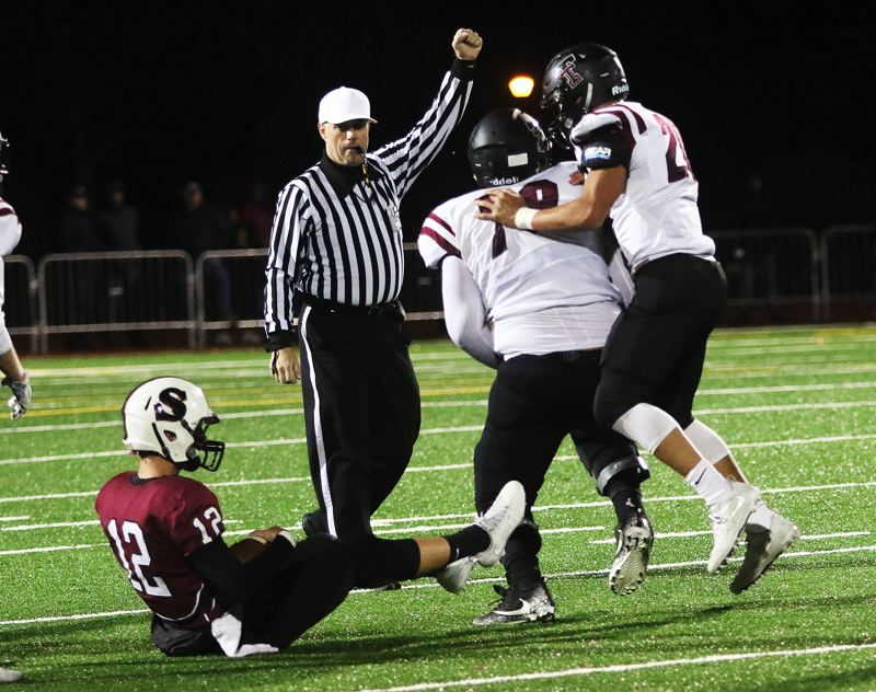 DAN BROOD - Tualatin senior lineman Gerald Saina (second from right) celebrates with sophomore John Miller after getting a quarterback sack in Friday's game.
