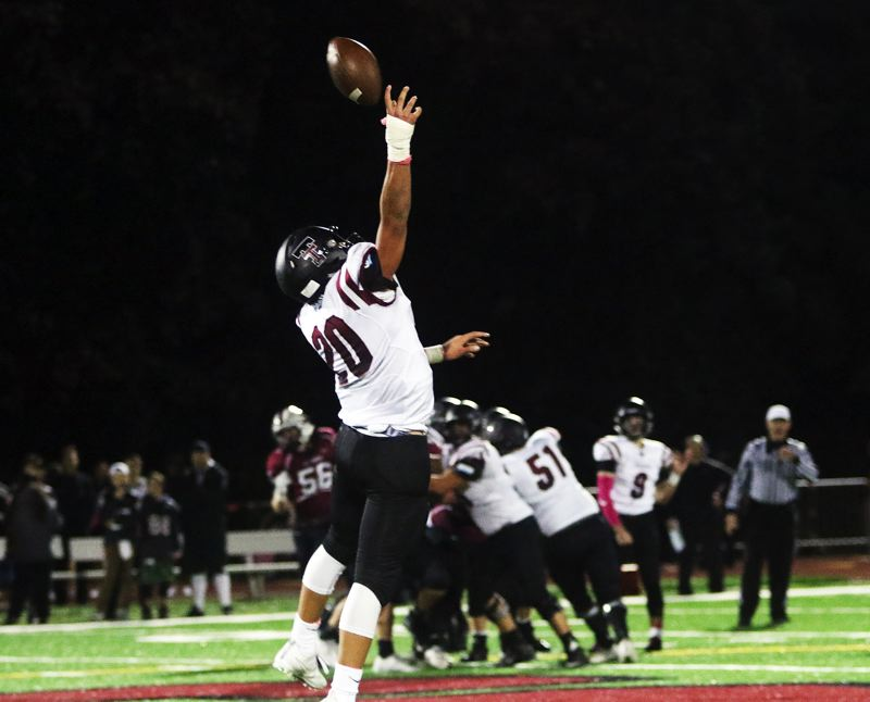 DAN BROOD - Tualatin sophomore John Miller leaps for a pass during Friday's game at Sherwood.