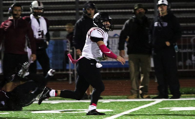 TIMES PHOTO: DAN BROOD - Tualatin junior quarterback Kyle Dernedde takes off on a 73-yard run, a play that set up his own 42-yard field goal and 20-12 lead over Sherwood in the Wolves' Friday home win.