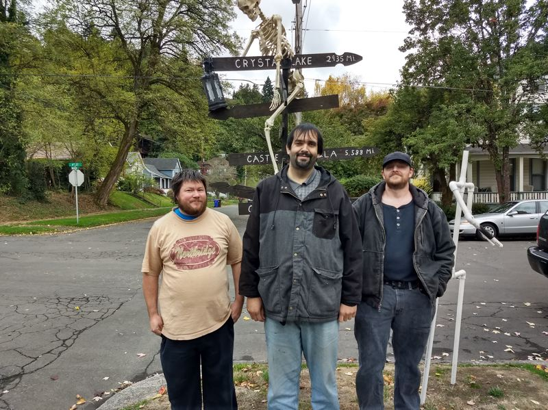 PHOTO BY PERSEPHONE HALEY - Phil Larose, Tim Ulsky, Josh Smith and a skeleton friend stand at the corner of Fourth and Madison in Oregon City where the three men put up an elaborate Halloween display every year.