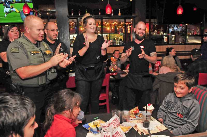 VERN UYETAKE - From left, law enforcement officers Michelle Rickles, Jason Ritter and Brad Moyle along with Red Robin staff members sing Happy Birthday to Jaden Aguilar.