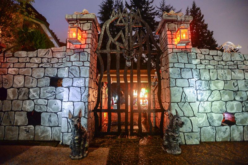OUTLOOK PHOTO: JOSH KULLA - Pumpkin Acres features an elaborate gate and wall comprising 32 separate pieces that bolt together. Behind the wall one can view the demonic glow of Halloween displays.