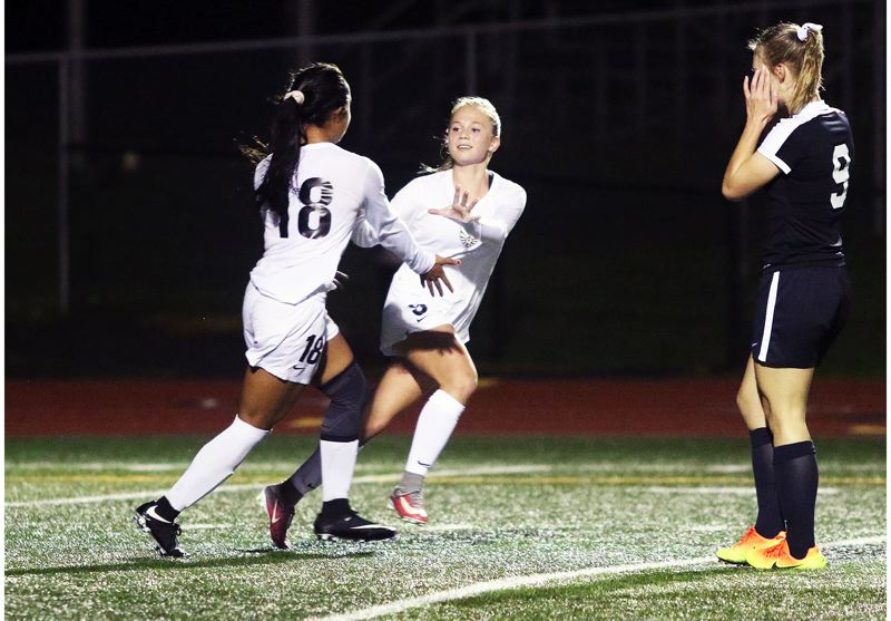DAN BROOD - Tualatin freshman Cally Togiai (left) and sophomore Hannah Olson celebrate following Togiai's second goal in the match with Sherwood.
