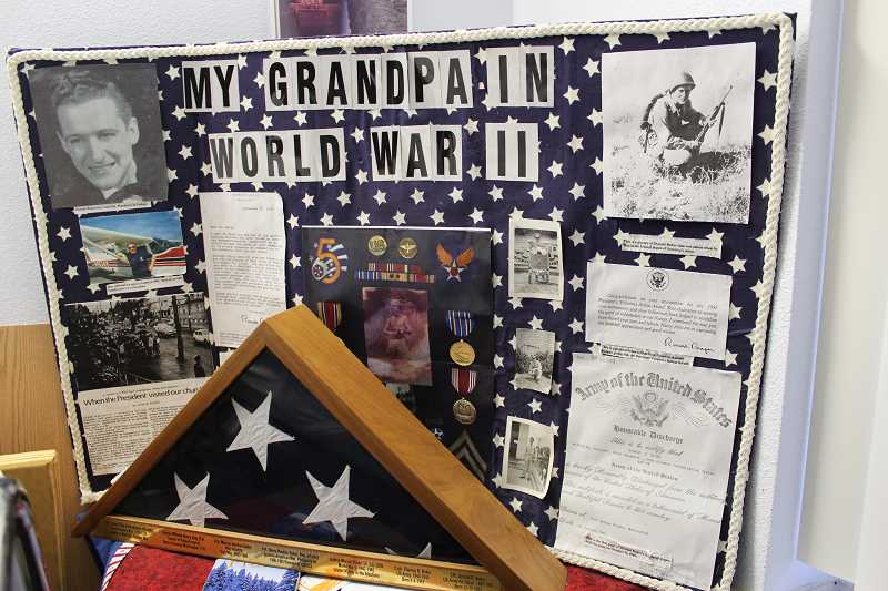 PIONEER PHOTO: KRISTEN WOHLERS - Don Baker's granddaughter made this poster, 'My Grandpa in World War II,' which features photos of the cryptographer, an honorable discharge certificate and letters from Ronald Reagan and Gerald Ford.