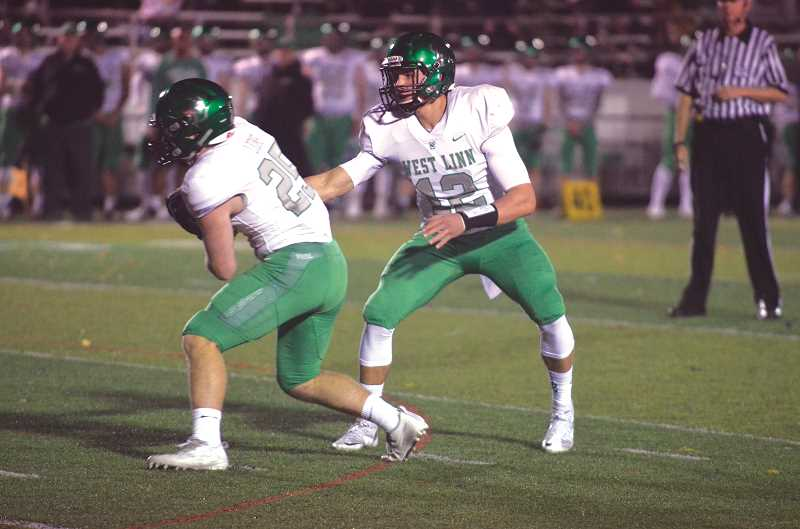 HERALD PHOTO: TANNER RUSS - West Linn quarterback Ethan Long hands the ball off to senior running back Tyler Good. Good would score a touchdown in West Linn's 49-7 drubbing of Canby on Oct. 27.