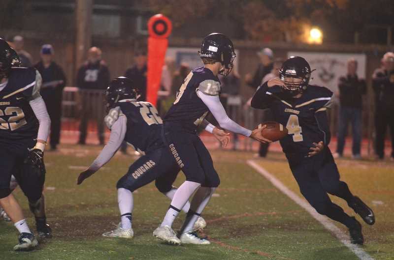 HERALD PHOTO: TANNER RUSS - Canby junior quarterback Trent Wakefield hands the ball off to senior running back Jacob Huggins. Huggins would score Canby's only touchdown in their 49-7 loss to West Linn on Oct. 27.