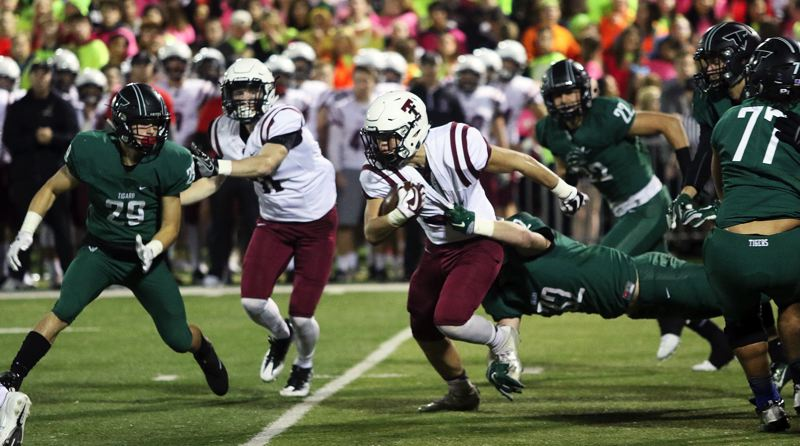 DAN BROOD - Tualatin sophomore running back Kainoa Sayre looks to pull away from Tigard junior Mitchell Cross during Friday's game.
