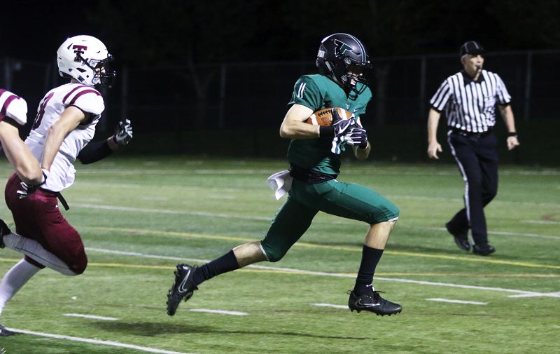 DAN BROOD - Tigard senior receiver Jakob Harrold heads toward the end zone during the first quarter of Friday's game. It would be the final play before the power went out at Tigard High School, causing the game to be moved to Tualatin.