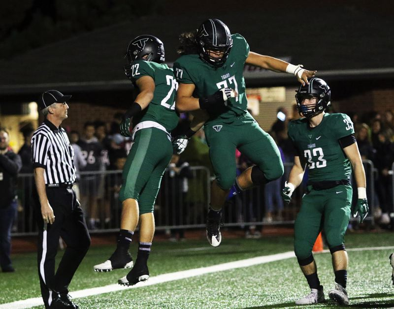 DAN BROOD - Tigard seniors Jake Leavitt (22) and Isaia Tavita Porter celebrate after Leavitt scored on a one-yard touchdown run in the first play after the game was moved to Tualatin High School.