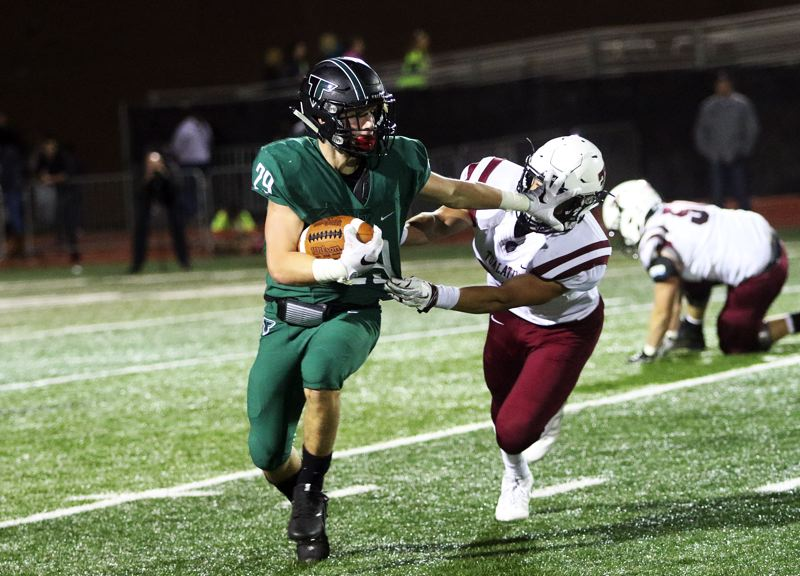 DAN BROOD - Tigard senior running back Spencer Smith looks to get away from a Tualatin defender in Friday's game.