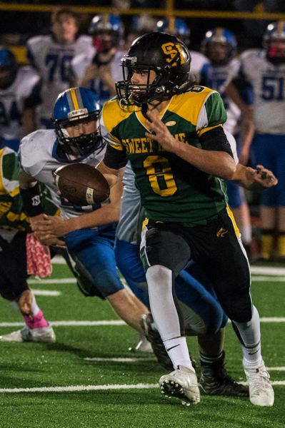 CENTRAL OREGONIAN PHOTO: LON AUSTIN - Sweet Home quarterback Colton Smith rolls out before hitting Jake Swanson in the corner of the end zone on an 18-yard strike — his fourth touchdown pass of the half — in his team's 52-6 home win over Crook County.