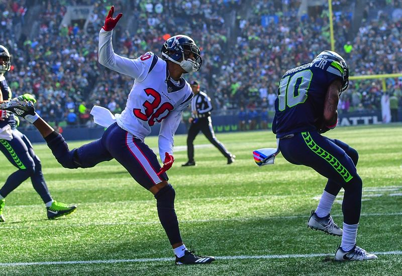 MICHAEL WORKMAN PHOTO - Paul Richardson (right) corrals a Russell Wilson pass before Houston's Kevin Johnson can get to the ball.