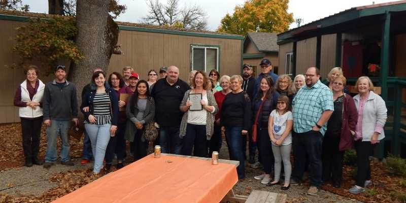 TIMES PHOTO: BARBARA SHERMAN - Caring Closet Executive Director Rose Money stands holding a plaque in the center of a group of Closet volunteers along with those who designed and built a new restroom and laundry room.