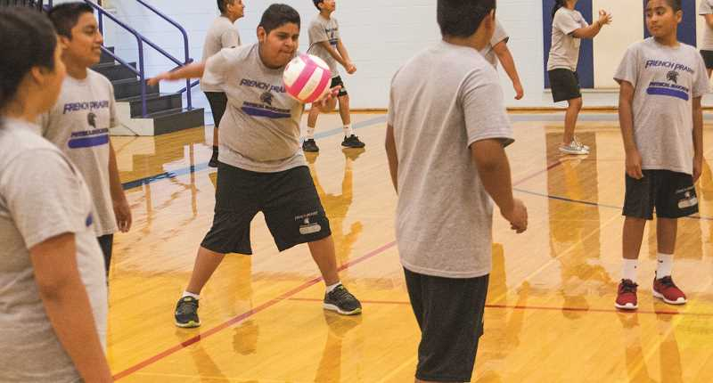 INDEPENDENT PHOTO: JULIA COMNES - This is the first year every French Prairie student has been provided a PE uniform free of charge. Pictured are seventh-graders playing volleyball during their Oct. 27 PE class.