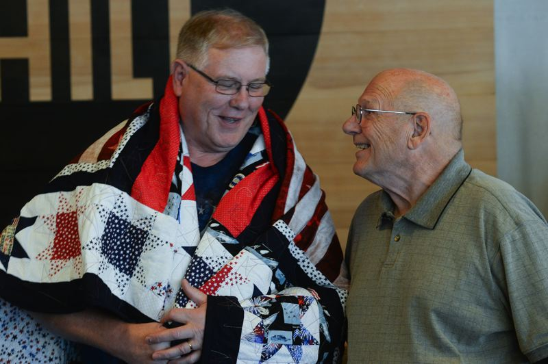 OUTLOOK PHOTO: JOSH KULLA - Veterans Steven and William Yung share a laugh Saturday at East Hill Church in Gresham as they receive special handmade quilts to celebrate their military service in the U.S. Navy and Air Force Reserve, respectively.