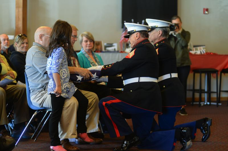 OUTLOOK PHOTO: JOSH KULLA - A U.S. Marine Corps honor guard presents folded American flags to military veterans Steven and William Yung Saturday morning at East Hill Church in downtown Gresham.