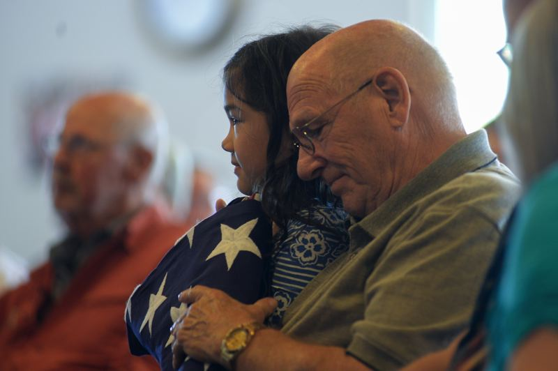 OUTLOOK PHOTO: JOSH KULLA - Steven Yung holds his folded American flag close to his heart along with his granddaughter Saturday at East Hill Church during a special ceremony honoring the military service of he and his brother William.