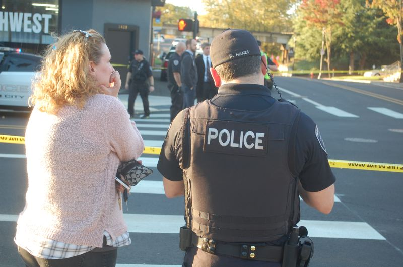PHOTO BY: RAYMOND RENDLEMAN - Oregon City Police Officer Dan Hanes interviews a witness to the Oct. 26 crash.