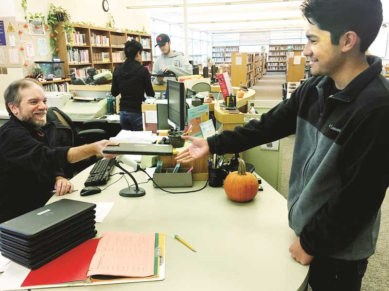 SETH GORDON - Newberg High School librarian Dale Conley hands out a new Chromebook laptop to a student in October. The school district distributed 1,050 of the devices so that each secondary student has their own to use for the school year.