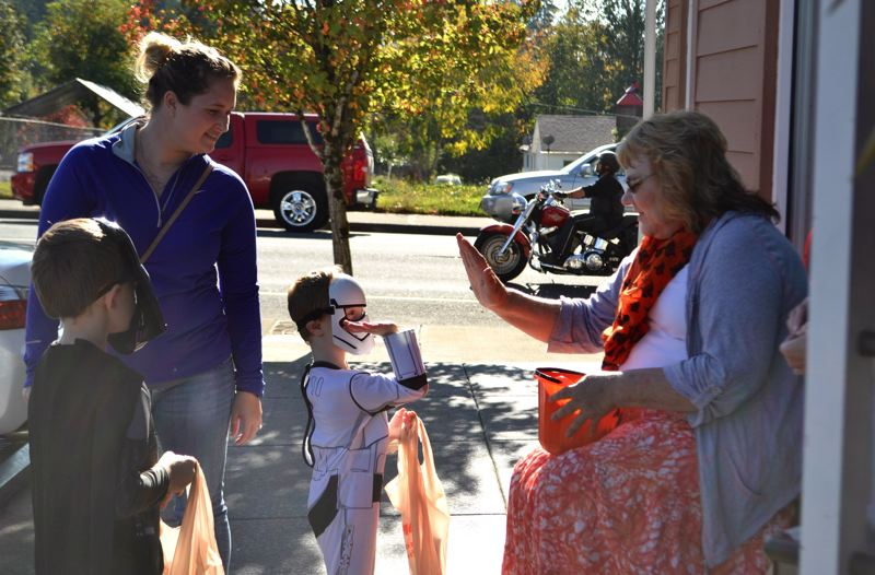 POST PHOTO: BRITTANY ALLEN - Marlene DePaolo, mother of Dolly's Pet Shoppe's Anna Judd, high-fives a courageous little storm trooper for his polite plea for candy.