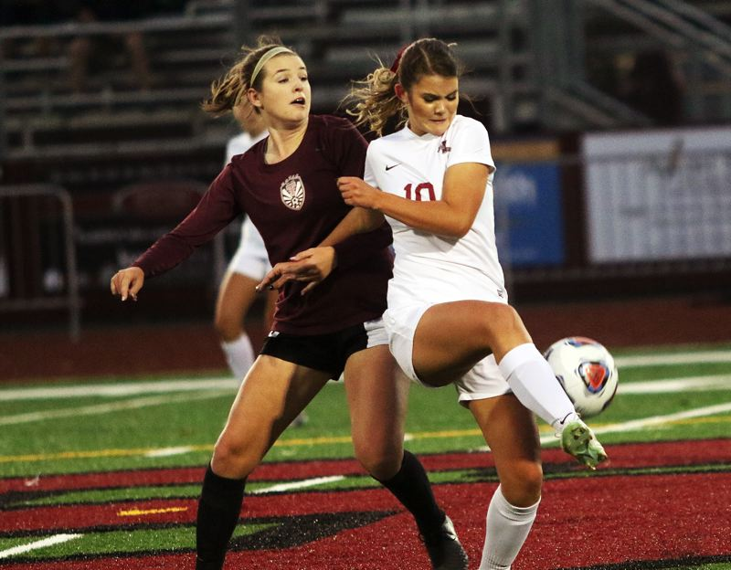 DAN BROOD - Sherwood senior Ashlyn Strohmaier (right) kicks the ball away while she's in front of Tualatin junior Megan MacPherson.