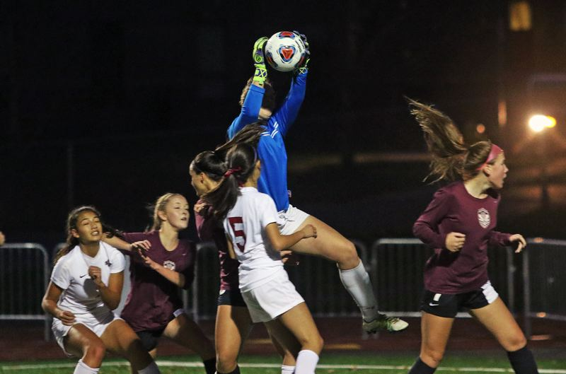 DAN BROOD - Tualatin's Sarah Hall goes up to grab a Sherwood corner kick.