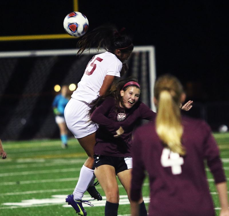 DAN BROOD - Sherwood junior Madi Pastores (left) goes up high to head the ball away from Tualatin's Skylar Maddox.