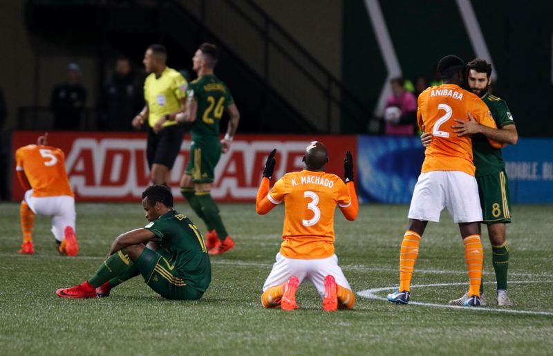 TRIBUNE PHOTO: JONATHAN HOUSE - Portland Timbers players react as the Houston Dynamo win on Sunday and advance in the MLS playoffs.