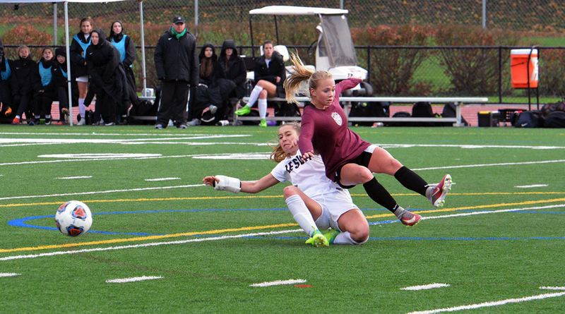 TIMES PHOTO: MATT SINGLEDECKER - Jesuit midfielder Ella Nelson tackles a Tualatin defender against Tualatin in the Class 6A playoffs.