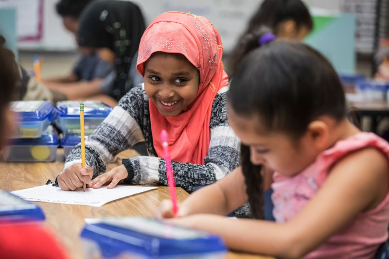 TRIBUNE PHOTO: JONATHAN HOUSE - First grader Safaa Awes smiles as she fills out her numbers chart at Mill Park Elementary School.