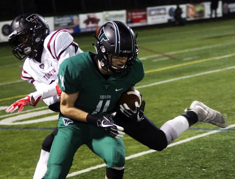 DAN BROOD - Tigard senior receiver Jakob Harrold looks to get up field after catching a pass in Friday's playoff game.