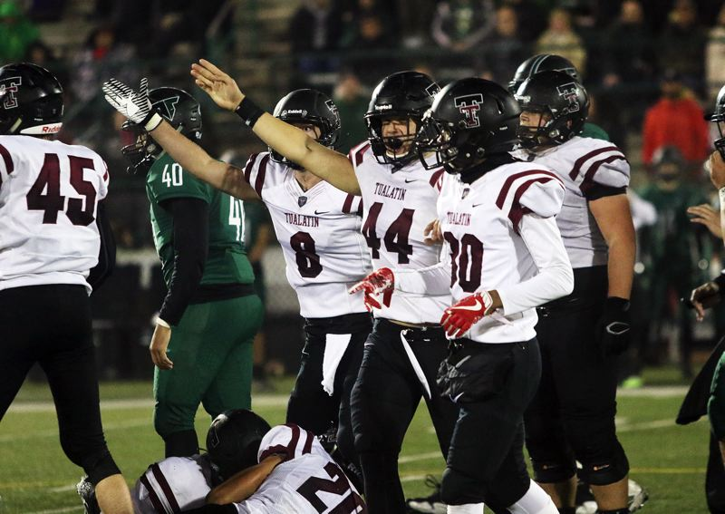 DAN BROOD - Tualatin's Chris Freese (8) and Adam Stubbs signal that it's the Wolves' ball following a fumble recovery by John Miller.