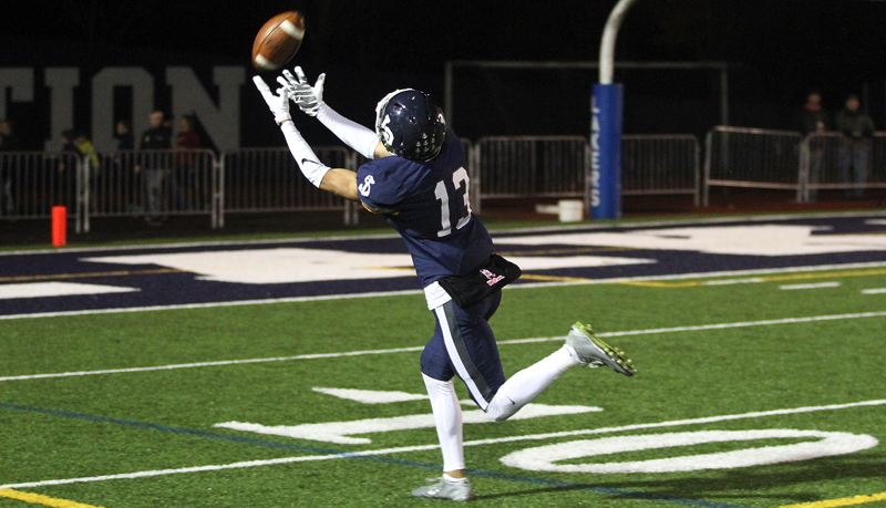 REVIEW PHOTO: MILES VANCE - Lake Oswego senior wide receiver Jordan Newlin makes a 46-yard touchdown catch on a throw from senior quarterback Ethan Long during their team's 45-0 home win over Sherwood in the second round of the Class 6A state playoffs on Friday night.