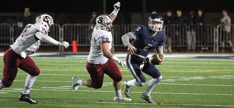 REVIEW PHOTO: MILES VANCE - Lake Oswego senior quarterback Jake Dukart looks to get away from Sherwood's Nick Severson during the Lakers' 45-0 win over the Bowmen in the second round of the Class 6A state playoffs on Friday night at Lake Oswego High School.
