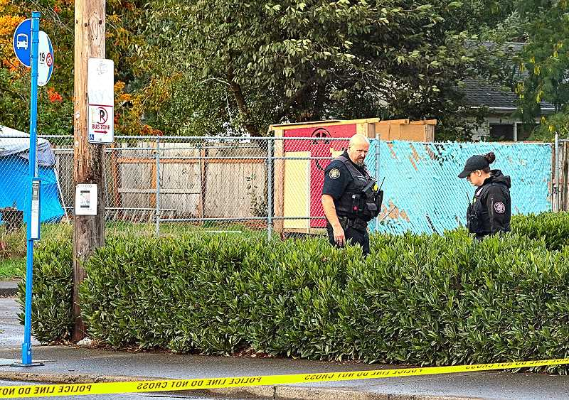 DAVID F. ASHTON - Officers look for evidence in a yard near where the bus stop shooting took place.