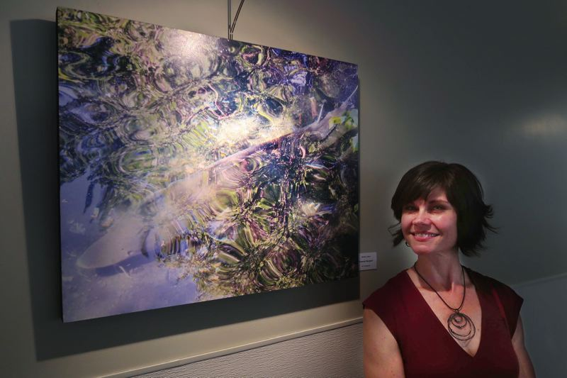 SUBMITTED PHOTO - Milwaukie resident Michelle Lattanzi stands next to one of her art photos; she will show her work at the Rain Spark Gallery opening on Nov. 16.