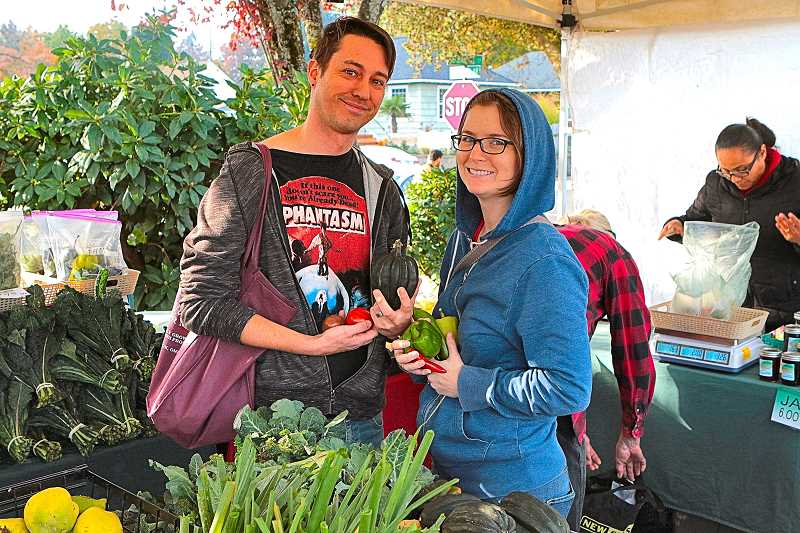 DAVID F. ASHTON - Happy to be shopping at the last Woodstock Farmers Market of the season were Colin Allrich and Rachel Desilets; here, they were buying from Greenville Farms.