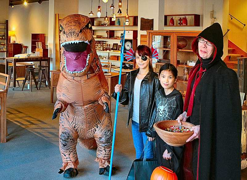 DAVID F. ASHTON - At The Joinery, puffy dinosaur David Ratzlaff welcomes trick-or-treaters Vika Czinger and Hadley Miller - who are treated by Riding Hood Sally Griffith.
