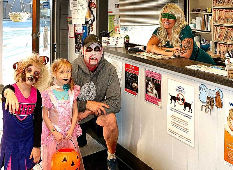 DAVID F. ASHTON - This costumed trio - Tennessee Violet Gray, Ava Maggio and Kendon Gray - gets treats from Hanora Bauer, inside VCA Woodstock Animal Hospital.