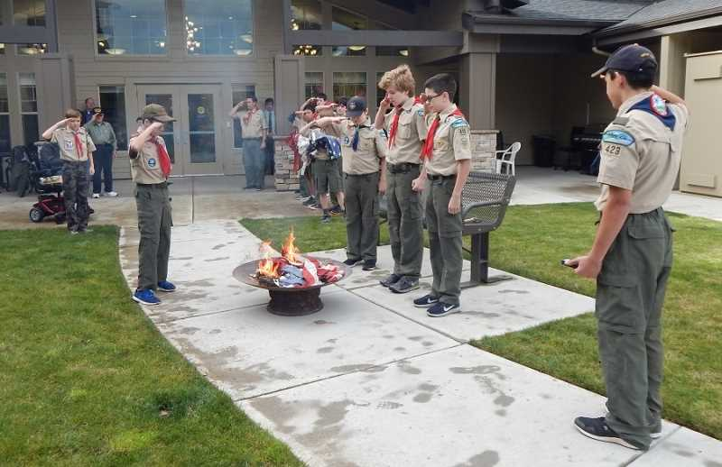BARBARA SHERMAN - Boy Scouts salute an American flag that they were retiring by carriying it in a folded position to a fire pit at Bonaventure, unfolding it and saluting it as it burned.