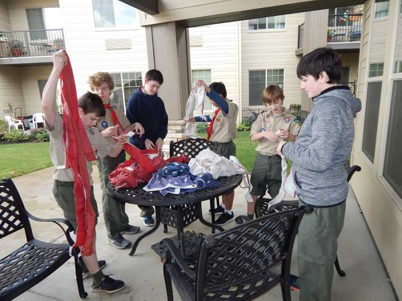 BARBARA SHERMAN - Boy Scouts carefully tear a flag's red and white stripes apart in preparation for retiring it by burning it in a fire pit, which is the best way to retire a flag.